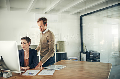 Buy stock photo Cropped shot of two colleagues working together on a computer in an office