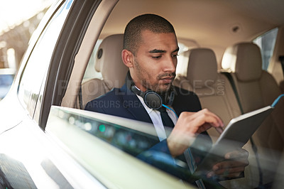 Buy stock photo Shot of a businessman using his tablet while sitting in his car