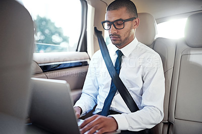 Buy stock photo Shot of a businessman using a laptop in the back seat of a car
