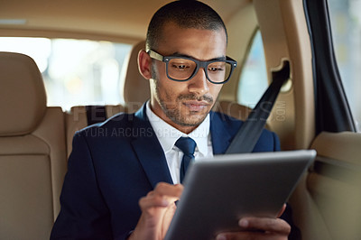 Buy stock photo Shot of a businessman using his tablet while sitting in the back seat of a car