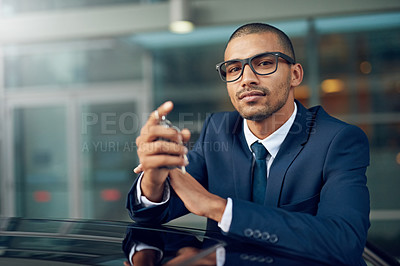 Buy stock photo Shot of a businessman leaning on his car outside
