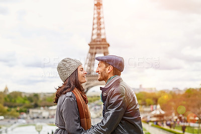 Buy stock photo Shot of a happy young couple kissing together in front of the Eiffel Tower