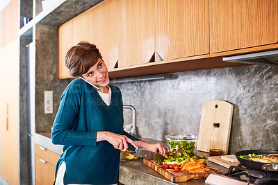 Buy stock photo Shot of a young woman talking on a cellphone while preparing food in her kitchen