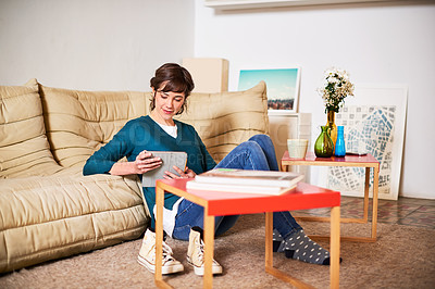 Buy stock photo Shot of a young woman sitting on her living room floor using a digital tablet