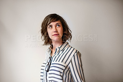 Buy stock photo Shot of an attractive young woman looking up while standing against a gray background