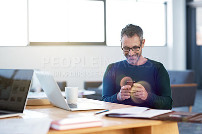Buy stock photo Shot of a man sending a text message while taking a work break