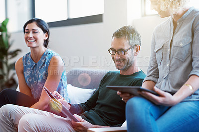 Buy stock photo Shot of a group of smiling colleagues talking together while sitting on a sofa in a modern office