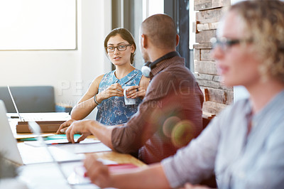 Buy stock photo Shot of two colleagues sitting a table talking together in an office