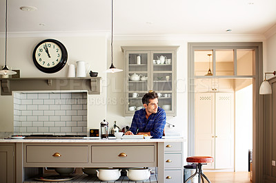 Buy stock photo Shot of a young man having breakfast and using a digital tablet in his kitchen