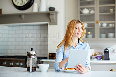 Buy stock photo Shot of a young woman leaning on her kitchen counter using a digital tablet