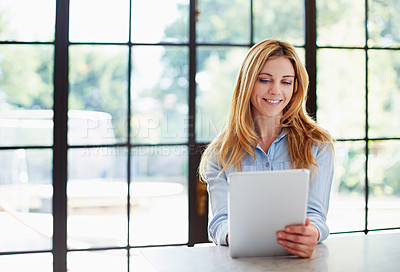 Buy stock photo Shot of a young woman leaning on her counter at home using a digital tablet