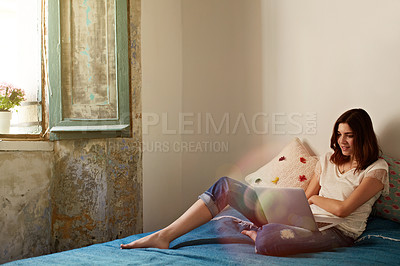 Buy stock photo Shot of a young woman lying on her bed using a laptop