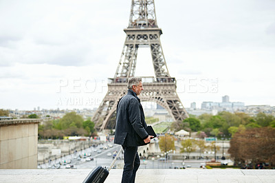 Buy stock photo Shot of a mature man walking with a suitcase in Paris with the Eiffel Tower in the background