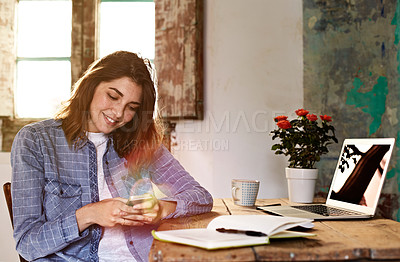 Buy stock photo Shot of a smiling young woman using a cellphone while sitting at a desk at home