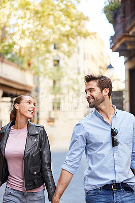 Buy stock photo Portrait of an affectionate young couple walking hand in hand together in the city
