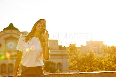 Buy stock photo Shot of an attractive young woman leaning on a wall on a cellphone with the city in the background