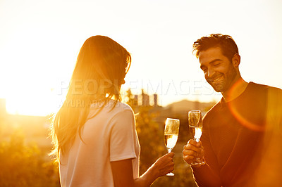 Buy stock photo Shot of a smiling couple drinking champagne while standing on their rooftop at sunset