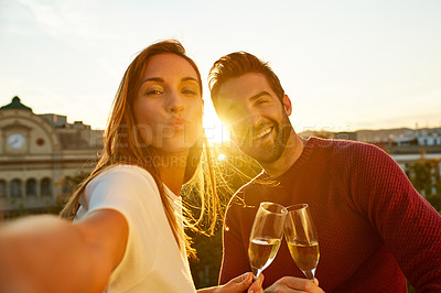 Buy stock photo Shot of a smiling couple drinking champagne and taking a selfie together while standing together on a balcony