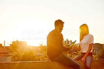 Buy stock photo Shot of a smiling couple drinking champagne while sitting on their rooftop at sunset