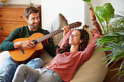 Buy stock photo Shot of a young man playing guitar for his girlfriend while relaxing in their living room