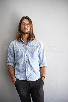 Buy stock photo Portrait of a smiling young man standing with his arms crossed against a gray background