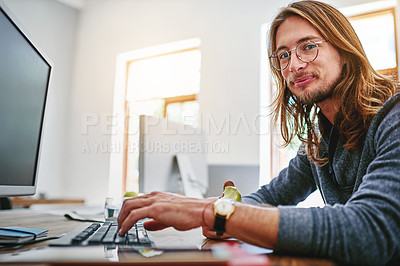 Buy stock photo Portrait of a smiling young man sitting at his desk in an office
