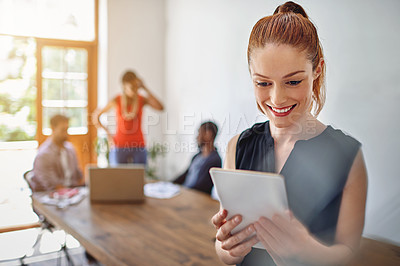 Buy stock photo Shot of a smiling young woman using a digital tablet in an office with colleagues in the background