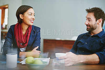 Buy stock photo Shot of two smiling colleagues talking together while sitting at a desk in an office