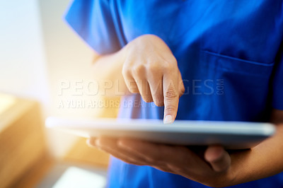 Buy stock photo Cropped shot of an unidentifiable young nurse using a tablet while standing inside a clinic
