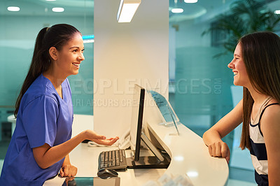 Buy stock photo Shot of a young nurse assisting a patient at the reception desk