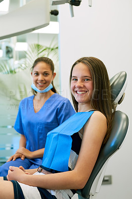 Buy stock photo Portrait of a young girl sitting in a dental chair with her dentist in the background