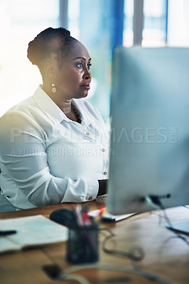 Buy stock photo Shot of a focussed businesswoman working behind her computer in the office