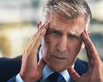 Buy stock photo Portrait of a tense businessman holding his head in the office
