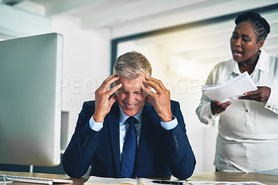 Buy stock photo Shot of an angry businesswoman berating her colleague while he sits at his desk