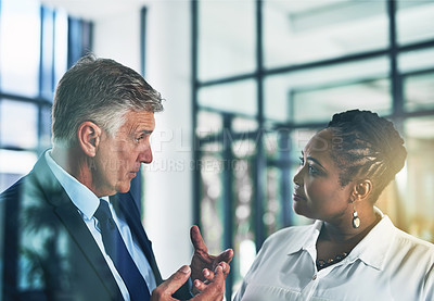 Buy stock photo Shot of two focussed businesspeople brainstorming together in the office