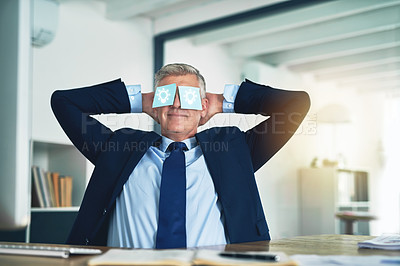 Buy stock photo Shot of a businessman relaxing behind his desk with adhesive notes over his eyes