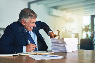Buy stock photo Shot of a frustrated businessman hitting a pile of paperwork with a hammer