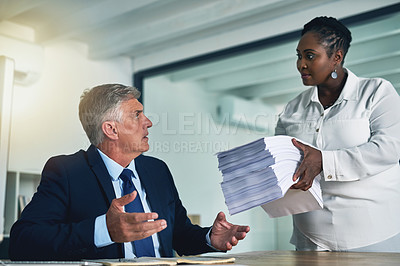 Buy stock photo Shot of a businesswoman handing a huge pile of paperwork to her overwhelmed colleague