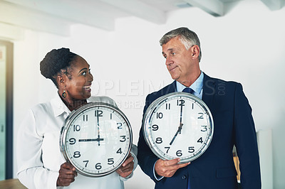Buy stock photo Shot of two businesspeople holding clocks while posing in the office