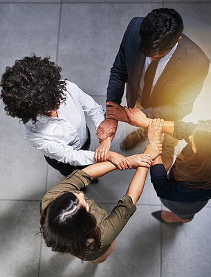 Buy stock photo High angle shot of a group of coworkers holding hands in the office