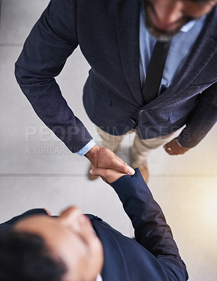 Buy stock photo High angle shot of two businessmen shaking hands in the office