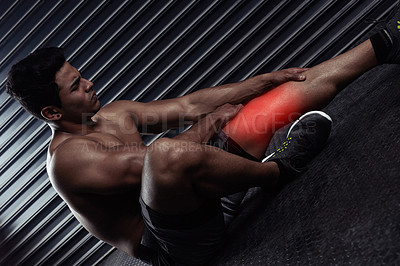 Buy stock photo Shot of an athletic young man sitting down with a knee injury during a workout