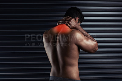 Buy stock photo Rearview shot of an athletic young man holding his neck in pain during a workout