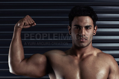 Buy stock photo Cropped portrait of an athletic young man flexing his bicep against a dark background