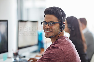 Buy stock photo Shot of a young man wearing a headset with his colleagues blurred in the background