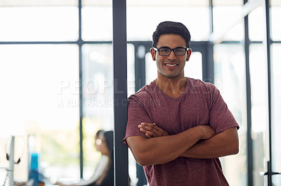 Buy stock photo Shot of a young businessman standing with his arms crossed in an office