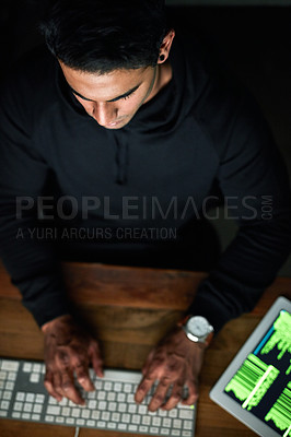 Buy stock photo High angle shot of a young hacker cracking a computer code in the dark