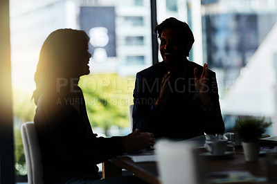 Buy stock photo Shot of two silhouetted businesspeople having a meeting in the boardroom