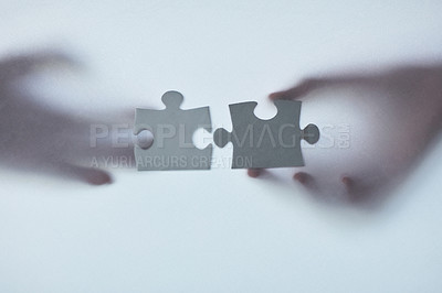 Buy stock photo Defocussed shot of two unrecognizable businesspeople holding two puzzle pieces together
