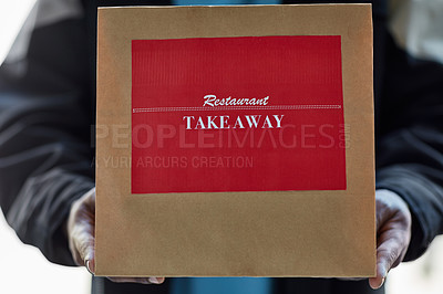 Buy stock photo Cropped shot of an unidentifiable delivery man holding a a restaurant takeaway